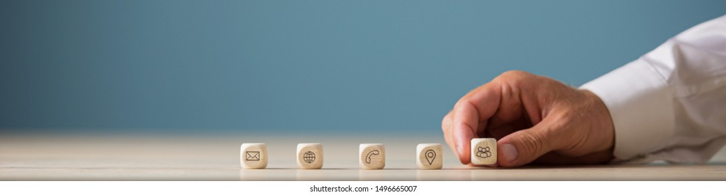Wide view image of hand of a businessman placing wooden cubes with contact, communication and location icons in a row.