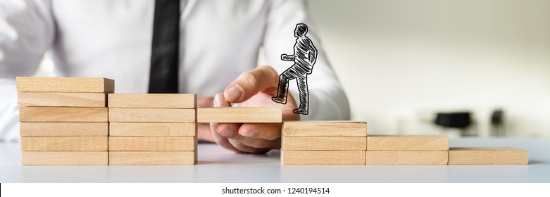 Wide view image of hand drawn shape of a businessman walking up the wooden steps supported by male hand. Conceptual of business teamwork and collaboration.