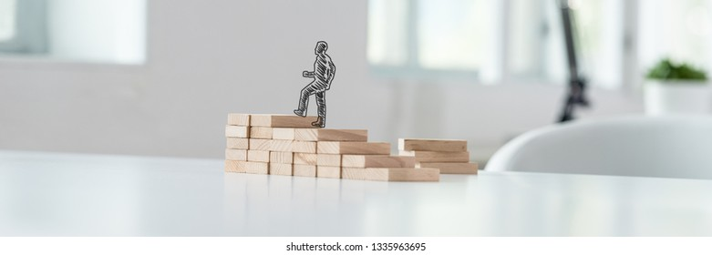 Wide view image of hand drawn silhouette of a businessman climbing up the steps made of wooden pegs on a business office desk.