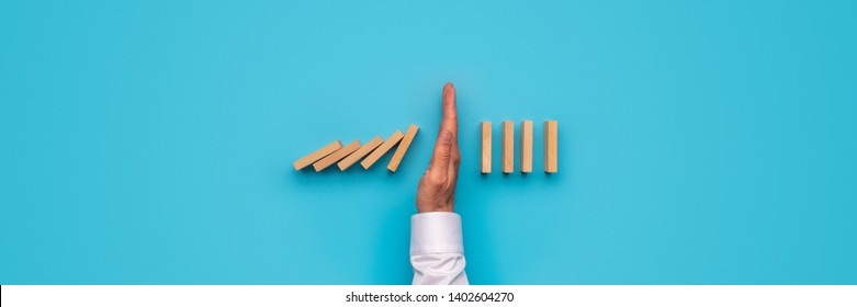 Wide view image of male hand stopping falling dominos. Over blue background.