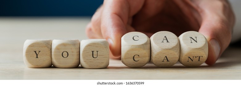 Wide view image of male hand changing a You cant sign in to a you can message. Spelled on wooden dices.