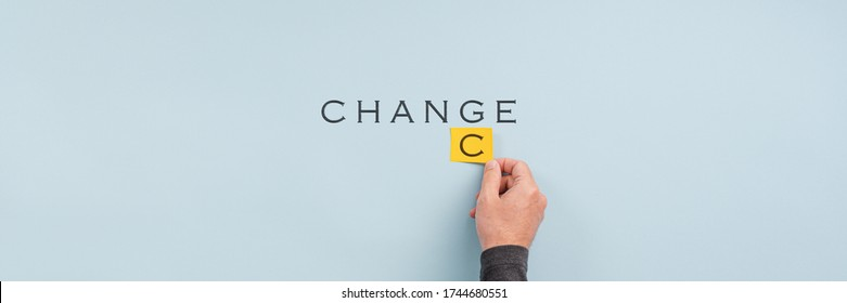 Wide view image of male hand changing the word Change into Chance in a conceptual image. Over light blue background with copy space.