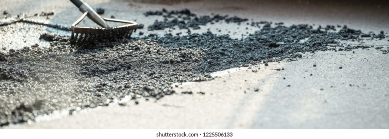 Wide view image of rakes arranging fresh asphalt mixture to cover and repair a crack in the road.