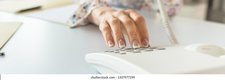 Wide view image of a secretary with perfect french manicure dialing telephone number using white landline phone.