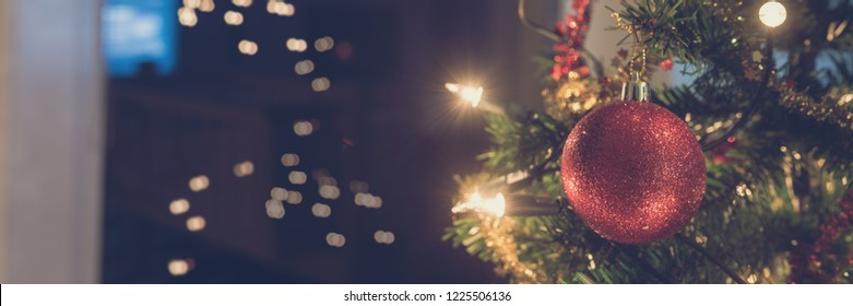 Wide view image of shiny red holiday bauble hanging on Christmas tree with lights on the tree and in background. With retro filter effect.