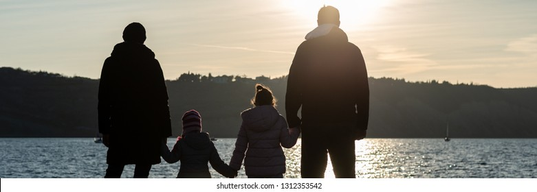 Wide view image of silhouette of a family with two kids holding hands by the sea looking in to the distance.