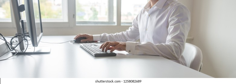 Wide view image of a student or programmer sitting at his desk working on office computer using keypad and mouse.