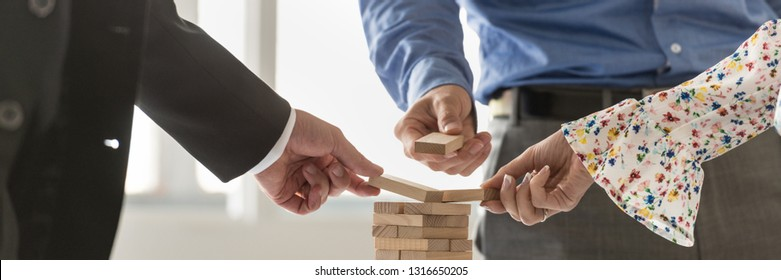 Wide view image of three businesspeople building a tower of wooden pegs in a conceptual image of business start up and teamwork.
