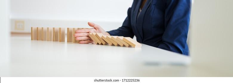 Das Bild einer unerkennbaren Geschäftsfrau, die an ihrem weißen Büroschreibtisch sitzt und dabei zusammenbricht, dominiert mit ihrer Hand in einem konzeptionellen Bild des Krisenmanagements.