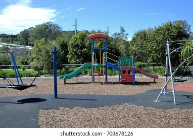Wide view of kids round swing attached with ropes to metal posts, plastic-made slides and other rides in park. Rubber surface and fragments of wood are laid in the park.