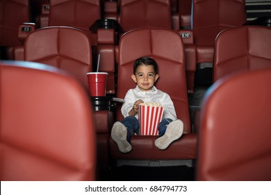 Wide view of a little kid eating popcorn and enjoying a movie while sitting in an empty cinema theater