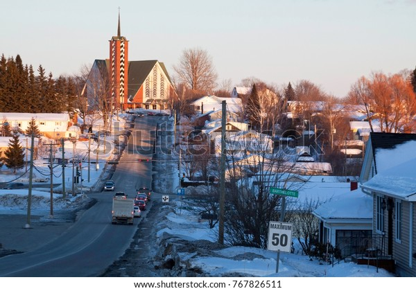 Wide view of a long street, with vehicles, leading up a hill to a church at the top, with a houses and buildings on either side, in Bathurst, New Brunswick, on a sunny day, blue skies, and clouds.
