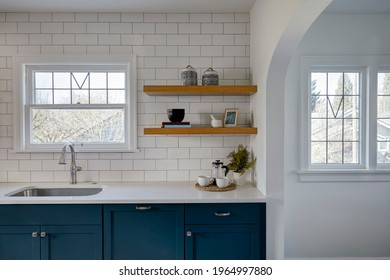 Wide view of newly remodeled kitchen with white tile and painted blue cabinets.