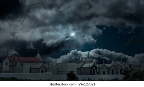 Wide view of an old european cemetery in a cloudy full moon night