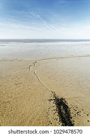 Wide view over a coastal landscape at low tide, dark stones in the foreground and gullies lead the view - Location: North Sea coast near Cuxhaven, Germany