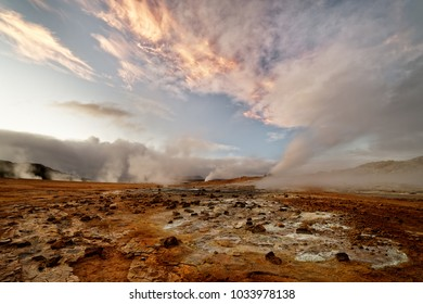 Wide view over a volcanic landscape with reddish ground, rising steam, above it a sky with a orange cloud formation - Location: Iceland, geothermal area 'Hverarönd' near the lake 'Myvatn'