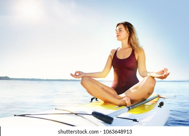 Wide view picture of a woman meditating on the sup board