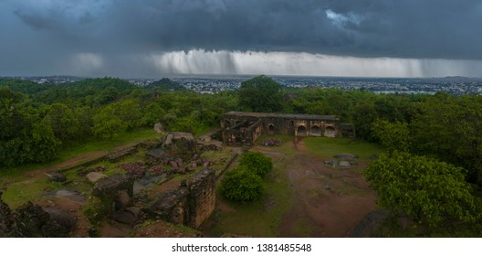 A wide view of rain clouds over a city with remains of a fort in the foreground. It is raining heavily over the city in the left of the frame gradually decreasing towards the right.