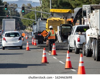 Wide view of raod construction site and a nan holding traffic sign that says SLOW .Bright orange traffic cones and trucks and cars are visible