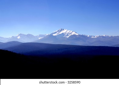 Wide view of a section of the snow-capped rocky mountains with trees in the foreground
