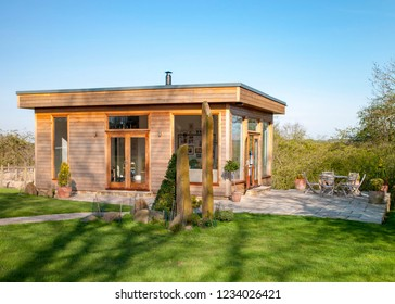 A wide view shot of a modern garden office on a bright summers day, a clear sky is above the wooden office and standing stones can be seen on the grass.