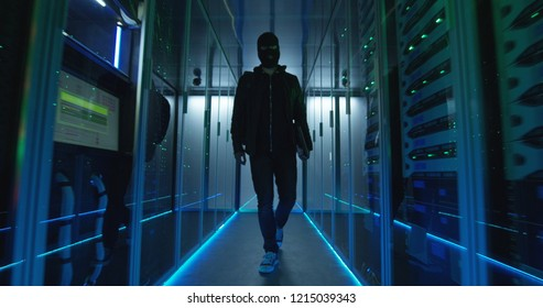 Wide view, slow motion shot of a masked hacker walking through corporate data center with rows of working rack servers