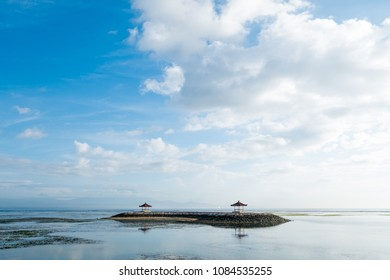Wide view of a small island with gazebos at morning time with low tide, Sanur, Bali, Indonesia