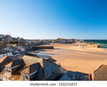 Wide view of St Ives town, beach and harbour as sunset approaches.