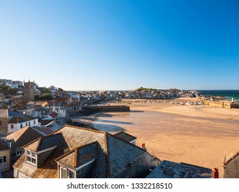Wide view of St Ives town, beach and harbour as evening approaches.