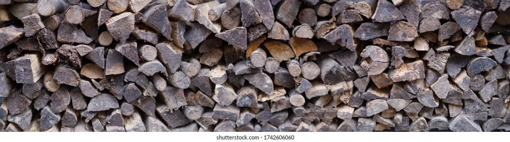 Breite Sicht auf gestapelte, unregelmäßig gespaltene Stämme für einen Ofen, Kamin oder Holzofen