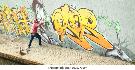 Wide view of street artist painting colorful graffiti on generic wall - Modern art concept with urban guy performing and preparing live murale with multi color aerosol spray - Retro vintage filter