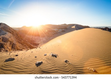 """Wide view of stunning sunset on sand formation at """" Valle De La Luna """" mountains in world famous Atacama desert Chile - Adventure travel concept to south america nature wonders - Warm sunshine filter"""