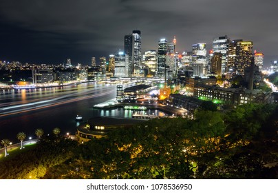 Wide view of Sydney CBD cityscape at night with light trails from ferry traffic in Circular Quay
