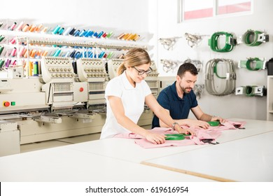 Wide view of two people getting some garments ready for embroidery in a textile factory