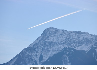 Wide view of a vapor jet trail over Mount Cheam, one of the largest mountains in southern British Columbia's Fraser Valley region.