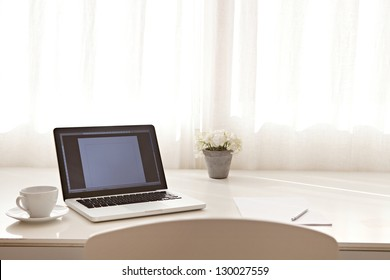 Wide view of a work desk interior with a laptop computer and white curtains on a sunny day.