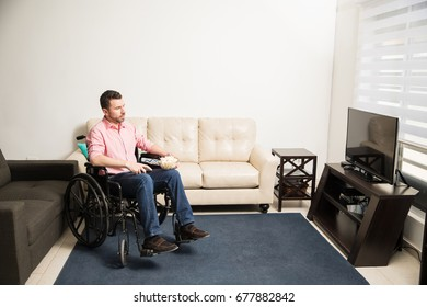 Wide view of a young man on a wheelchair looking sad and depressed while watching the tv at home