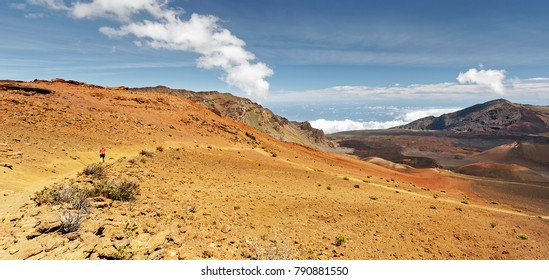 "Wide volcanic landscape with lava fields in different colors, ocher shades, reds, person as size comparison, cloud formation - Location: Hawaii, Island Maui, volcano ""Haleakala"" (Haleakal?)"