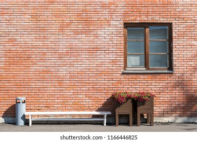 Wide window with wooden frame on red brick house facade with white bench, trash can and two pots of flowers on both sides with empty space