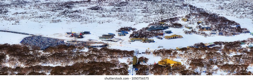 Wide winter panorama of Perisher valley town in Snowy Mountains of NSW, Australia. Peak of winter skiing season with lots of snow and tourists in elevated aerial veiw over Perisher infrastructure.