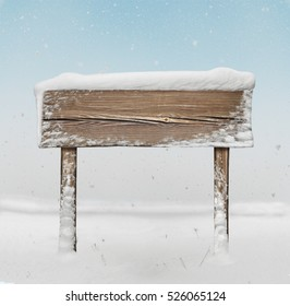 Wide wooden signpost with snow on it and snowfall on background