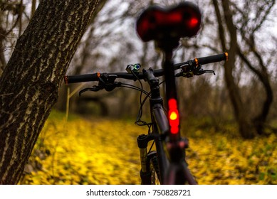 Wide-Angle Closeup of Red Bicycle Tail Light Illuminated on Bike Frame Left with Green Grass, Trees and Lake Out of Focus in the Background Beneath a Cloudy Overcast Sunset