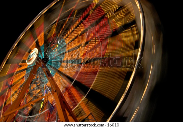 Wide-angle ferris wheel at night to show motion light blurs.