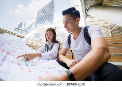 Wide-angle front view of cute smiling young Asian couple tourists sitting on the stair while holding paper metro map together with a woman pointing to map on vacation with tall building background