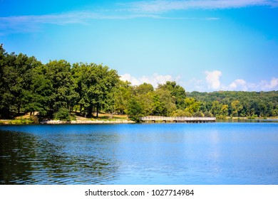 Wide-angle photograph of Kensington Metro Park's summer landscape in Milford, Michigan. Division between water, bunches of vibrant green trees and vivid blue sky loosely follows the rule of thirds.