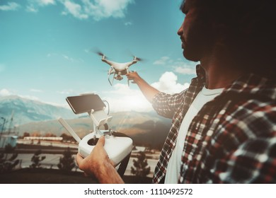 Wide-angle shot of a bearded man in plaid shirt with the remote controller in one hand releasing flying drone from another hand to film the mountains and hills behind him during sunny summer day