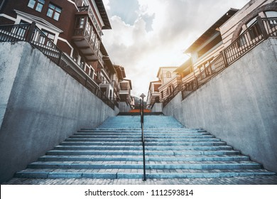 A wide-angle shot from the bottom of a colorful staircase stretched into the vanishing point, with European narrow street in the distance; bluish stairs in urban settings surrounded by hotel buildings