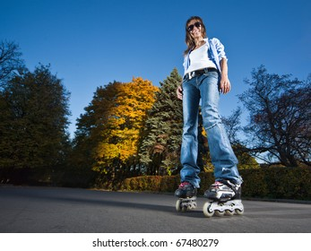 Wide-angle shot of a happy rollerblading girl