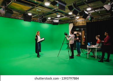 A wide-angle shot of a multi-ethnic group of people working in a film studio, a mature caucasian woman can be seen presenting in front of a green screen.