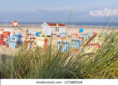 Wide-angle shot of traditional baltic beach chars on a wonderful dune beach on the North Sea island Langeoog in Germany with blue sky, clouds, sand and grass on a beautiful summer day
